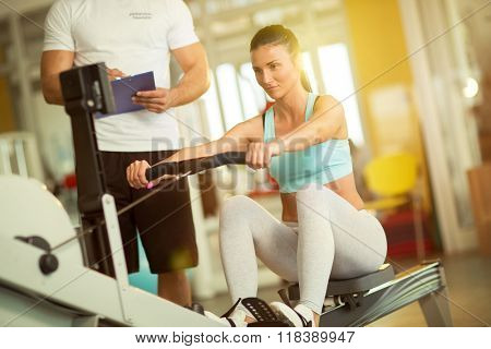 Fit woman working out on row machine her trainer taking notes in gym