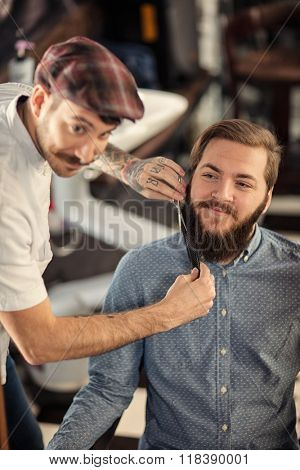 smiling hairdresser shaving with scissors and combs of satisfied client