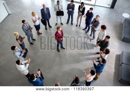 Top view on enthusiastic business team with leader in centre of circle