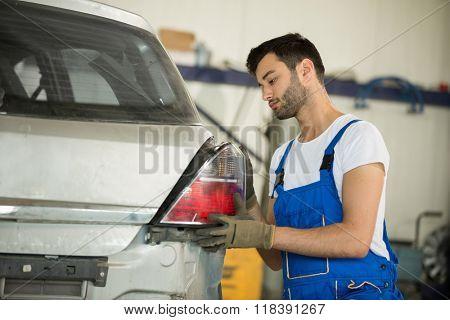 Mechanic fixes backlight on car