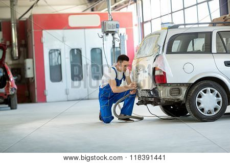 Car painter prepare body part for paint