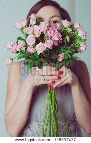 Wedding bouquet of flowers, young bridesmaid holding a bouquet of pink roses, and looking over the flowers