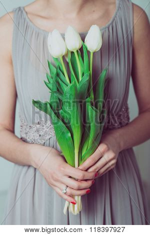 Wedding bouquet of tulip flowers, young bridesmaid holding a bouquet of white tulips.