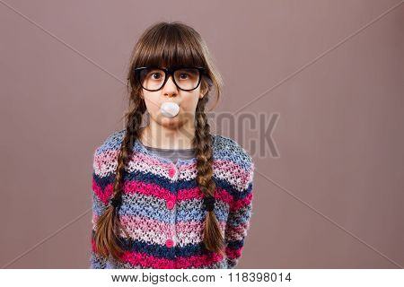 Little nerdy girl blowing bubble gum