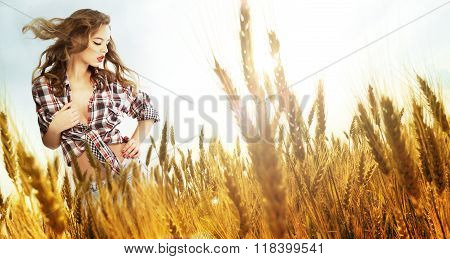 Woman standing in a wheat field; sunny summer day lens flare