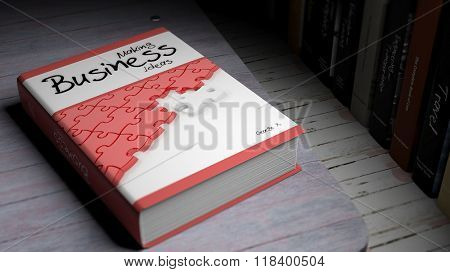 Hardcover book on Making Business with illustration on cover, on wooden surface.