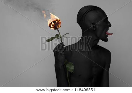 Gothic And Halloween Theme: A Man With Black Skin Holding A Burning Rose, Black Death Isolated On A