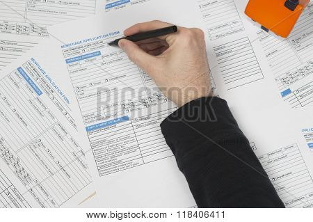 Male hand filling in mortgage application form