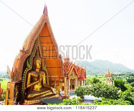 A view from the top of the pagoda golden buddha statue with rice fields and mountain Wat Tham Sua(Tiger Cave Temple) Tha Moung Kanchanburi Thailand