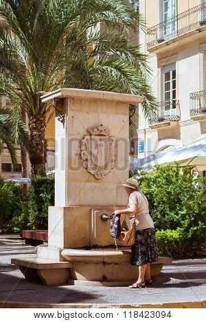 Elderly Woman Collects Water In Fountain On Popular Tourist Street, Alicante, Valencia, Spain