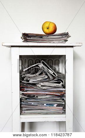 Stack Of Newspapers On The Nightstand And An Apple