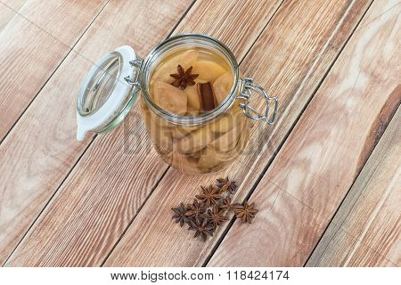 Preserved Pear Compote With Star Anise And Cinnamon In Glass Jar On Wooden Background