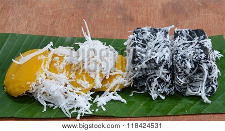 toddy palm cake topping and black coconut sweet pudding on banana leaf