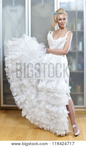 The young woman with a wedding dress in hands dreams about wedding