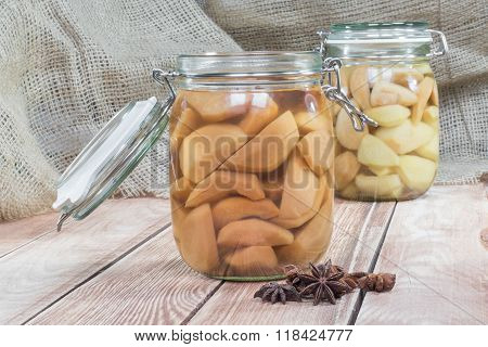 Two Preserved Pear Compote In Glass Jar On Wooden Table With Star Anise