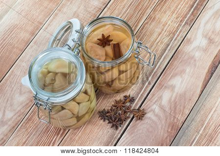 Two Preserved Pear Compote With Star Anise And Cinnamon In Glass Jar On Wooden Background