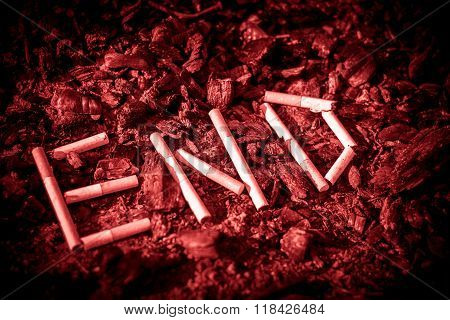 The earth is strewn with ash and ash. On the ground lay a broken cigarette. Lined and form words.
