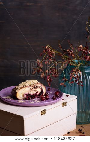 Piece of almond cake, cranberry dessert, chocolate roll, served with fresh cranberry.