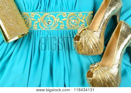 Gold High-heeled Shoes, Clutch Bag And Blue Dress With Gold Accentson. Top View