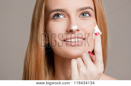 Blond Woman Using Moisturizer.