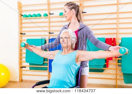 Senior woman in wheel chair doing physical therapy with her trainer