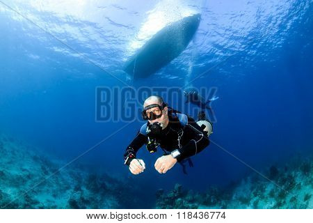 SCUBA diver below a boat