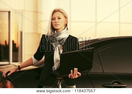 Young fashion business woman with laptop standing by her car