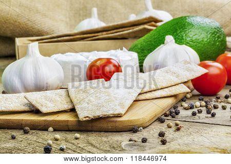 Crispbread with tomatoes, garlic, avocado and cheese