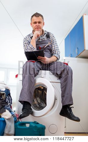 Repairman is repairing a washing machine on the white background. Entering malfunction sitting on wa