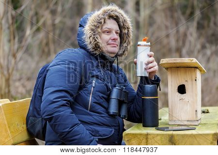 Ornithologist drinking tea in park near wooden bird cage