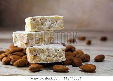 Italian Nougat And Almonds On A Rustic Wooden Table, Close Up With Copy Space