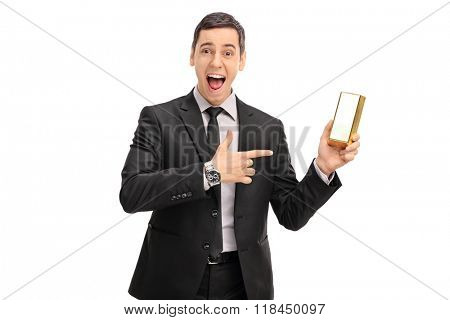 Ecstatic businessman holding a gold bar and pointing towards it with his finger isolated on white background