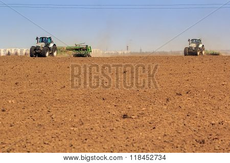 Panorama Of Two Tractors Sowing In Field