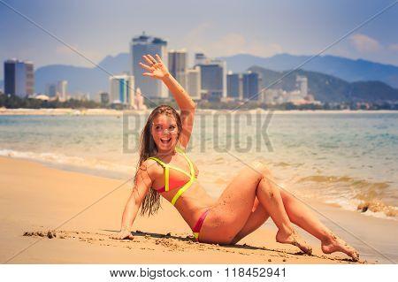 Blonde Girl In Bikini Sits Bent Knees On Wet Sand Waves Hand