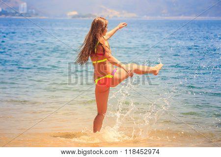 Blonde Slim Girl In Bikini Steps Into Sea Splashes On Beach