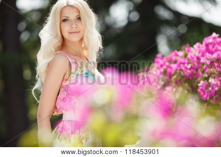 Beautiful woman on the terrace of white with pink flowers