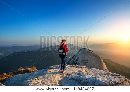 Woman Stands On The Peak Of Stone In Bukhansan National Park,seoul In South Korea And Watching To Su