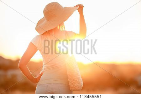 Woman in hat with large fields, at sunset
