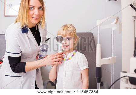 Little girl checking her vision in doctors office