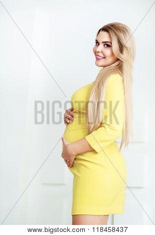 beautiful pregnant blond woman, wearing a yellow dress, studio shot