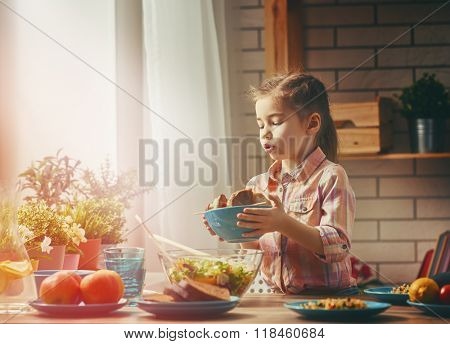 Cute little  child girl sets the table for dinner. Healthy food at home.