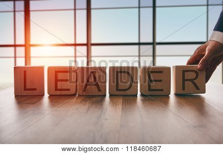 the concept of leadership. hand men in business suit holding the cubes which the written word leader.