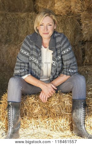Attractive middle aged blond woman sitting on a hay bale in a barn wearing boots