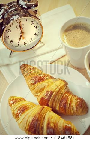 A continental breakfast of croissant pastries and coffee Illuminated with golden early morning sunshine and accompanied by a classic alarm clock set at seven o'clock