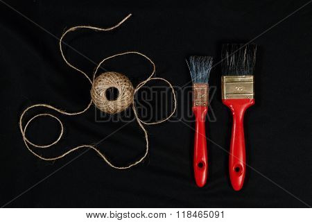 Packthread And Two Red  Paint  Brushes On Black Background