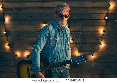 Senior Bearded Guitarist Holding Guitar Standing In Front Of Wooden Wall With Light Bulbs.
