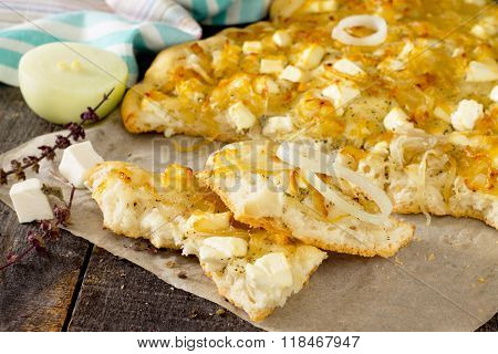 Focaccia With Cheese And Caramelized Onions On A Wooden Table