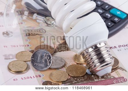 Energy saving concept. Electric light bulb, ruble money and calculator