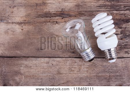 two types of light bulbs on wooden background