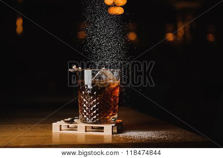 Dusting Whiskey Drink With  Ice  On  Wood In Bar
